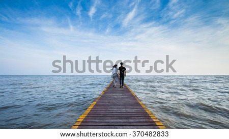 Two lovers walking on the bridge at the sea and holding themselves by hands