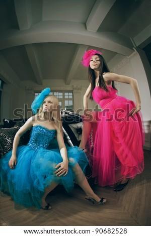 Two luxury fashion woman in vintage interior - stock photo