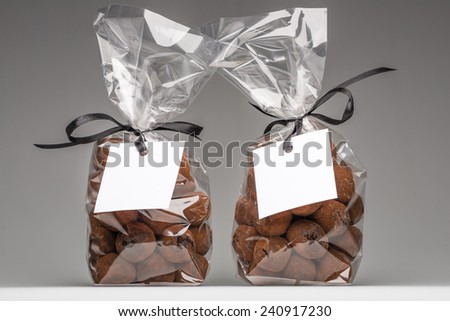 Two luxury plastic bags with elegant black ribbons of chocolate truffles. Blank label that you can add your own trademark or your own message. Christmas gifts. Shooting on grey background in studio. - stock photo