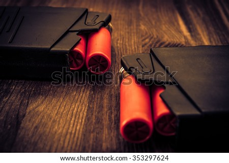 Two magazines with red cartridges 12 gauge lie opposite each other on the wooden table. Close up view, focus on background, image vignetting and the yellow-blue toning - stock photo