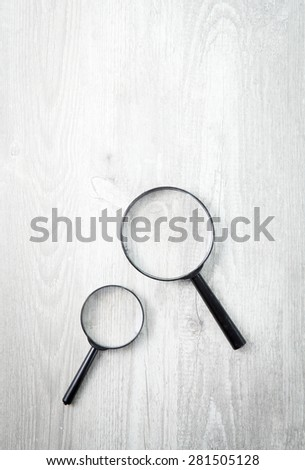 Two magnifying glass on white wood table, Search symbol - stock photo