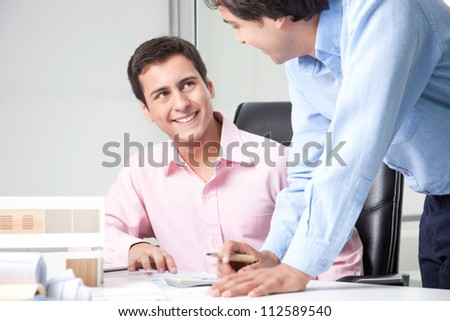 Two male architect at workplace with blueprints.