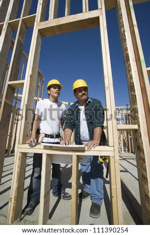 Two male architects with blueprint discussing at a construction site - stock photo