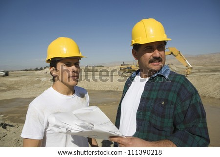 Two male architects with blueprint discussing at construction site