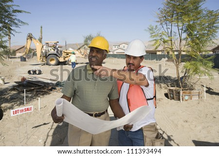 Two male architects with blueprint discussing at construction site - stock photo