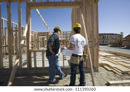Two male architects working together at construction site - stock photo