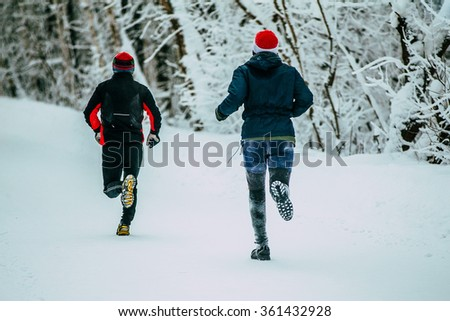 two male athlete running on winter alley in Park during  marathon. snow and cold weather - stock photo