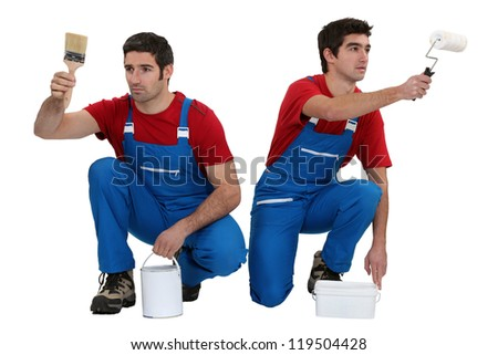 Two male decorators working in unison - stock photo