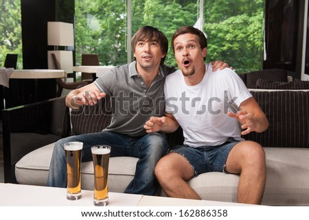 Two male football fans cheering football team. Drinking bear in pub, green trees on background   - stock photo