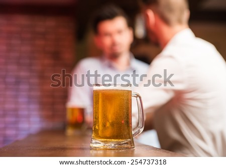 Two male friends in a pub with glasses of beer. Focus on a glass of beer.