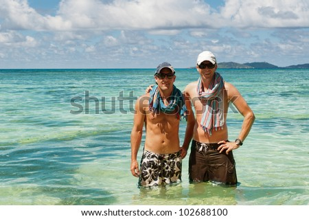 Two male friends on tropical island in water. Beautiful tropical vacation in the warm sunny Seychelles island oceans and palm trees - stock photo