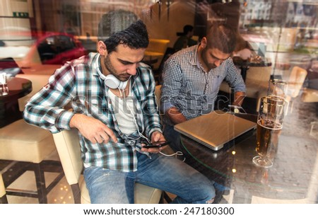 Two male friends sitting at the cafe and using smartphone. Addicted to social networking.Image taken from outside trough glass. - stock photo