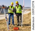 Two male geodesist with tacheometer checking plans standing by highway - stock photo