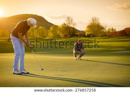 Two male golf player at sunset on green, one putting , with beautiful fairway in background. - stock photo