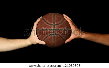 Two male hands holding basketball, image on black background. - stock photo