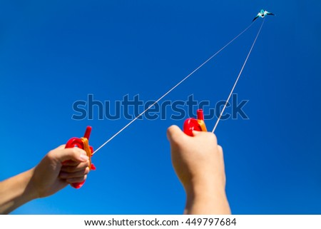 Two male hands holding kite strings with a kite  in sky at distance