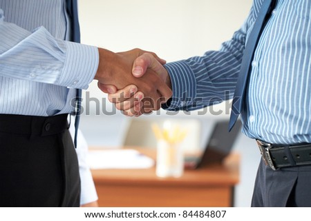 two male hands in business handshake, both wear blue shirts - stock photo