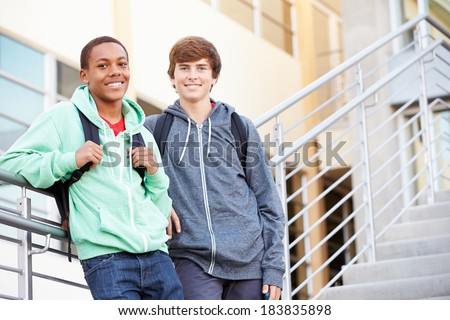 Two Male High School Students Standing Outside Building - stock photo