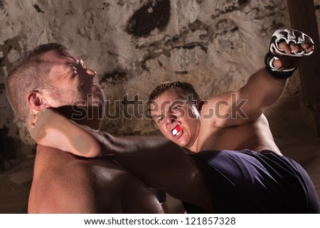 Two male mixed martial artists fighting indoors - stock photo
