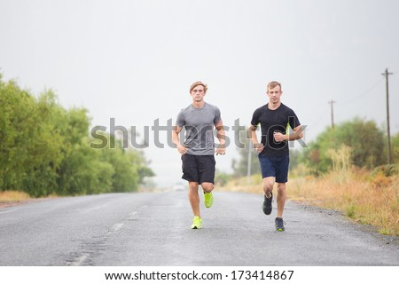 Two male models running on a tarmac road, bare chested and wearing shorts and running shoes.