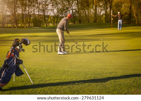 Two male senior golf player putting on green at twilight, with golf bag in foreground. - stock photo