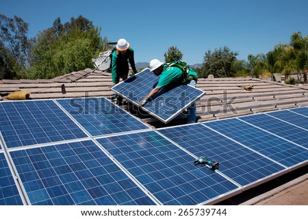 Two male solar workers install solar panels on home in Oak View, Southern California  - stock photo