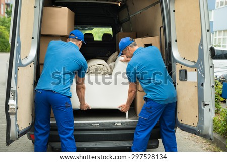 Two Male Workers In Blue Uniform Adjusting Sofa In Truck - stock photo