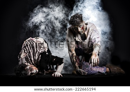Two male zombies crawling on their knees, on black smoky background, looking at camera. Halloween theme - stock photo