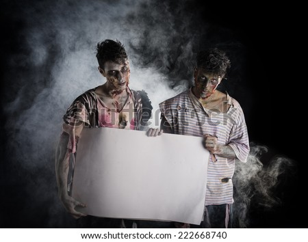 Two male zombies holding empty white banner, large copy-space for Halloween - stock photo