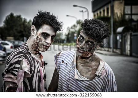 Two male zombies standing in empty city street looking at camera - stock photo