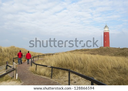 Two man are walking to red lighthouse - stock photo