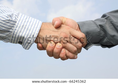 Two man hands handshake on sky background