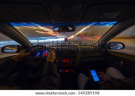 Two man in a car moves at fast speed at the whinter night. Blured road with lights with car on high speed.