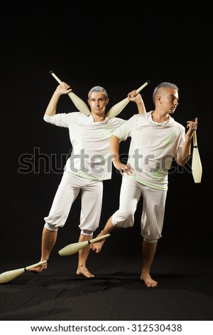 Two man juggling clubs isolated black background