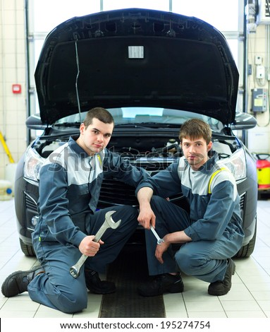Two man mechanics working under the hood of a car - stock photo