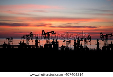 two man on oilfield with pump on sunset background - stock photo