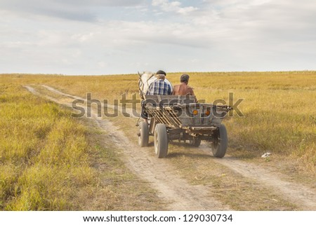 Two man on old wooden cart - harvest time on Ukraine. - stock photo