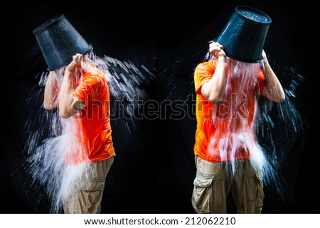 two man pour a bucket of ice topped their head on a black background. - stock photo
