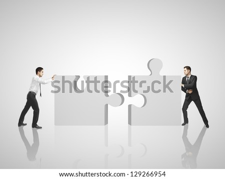two man puts puzzle on room - stock photo
