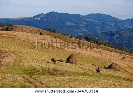 Two man rids horses on valley on mountain background - stock photo