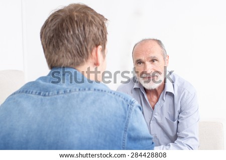 Two man talking while the father is smiling and you can see the son from the back - stock photo