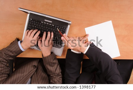 two man working with laptop. one is typing, another is pointing at the screen