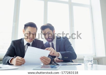 Two managers discussing contract in meeting room - stock photo