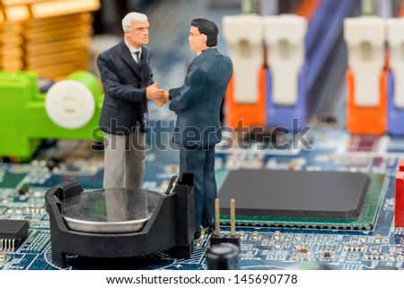 two managers talk on the motherboard of a computer standing - stock photo