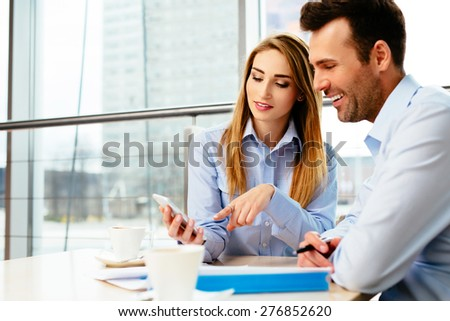 Two managers testing a mobile app in an office - stock photo