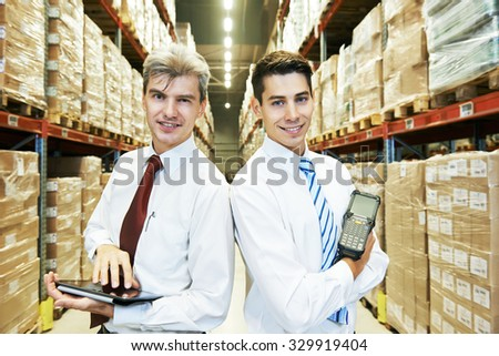two managers workers in warehouse with tablet computer  - stock photo