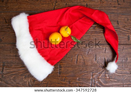 Two mandarin on a Christmas hat. - stock photo