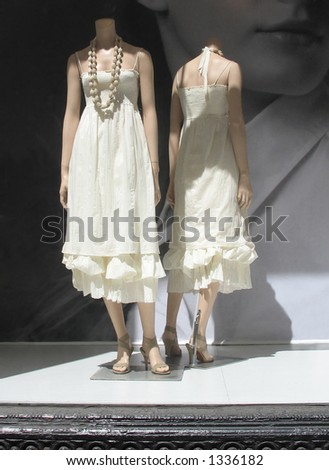 Two mannequins in storefront window - stock photo