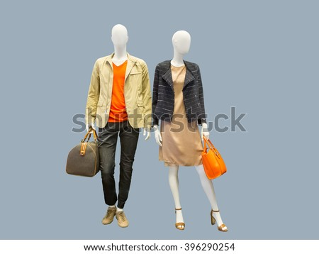 Two mannequins, male and female, dressed in casual clothes. Isolated on grey background - stock photo