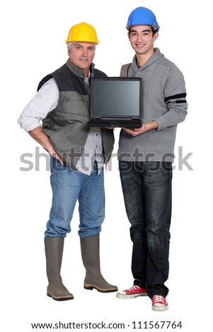 Two manual worker with a laptop. - stock photo